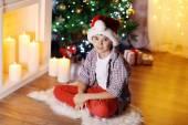 Little boy sitting near fireplace in room — Stock Photo