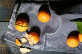 Juicy ripe tangerines with leaves on wooden table  — Stock fotografie