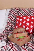 Hand-made Christmas gifts and decorations on plaid in room — Stock Photo