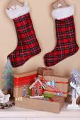 Hand-made Christmas gifts and decorations on fireplace in room — Stock Photo