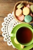 Colorful macaroons with cup of tea on wooden background — Photo