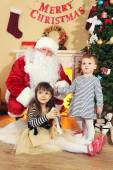 Santa Claus with two little cute girls near  fireplace and Christmas tree at home — Stock Photo