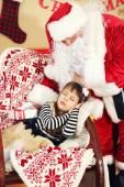 Papai Noel dando presentes para dormir pouco bonita árvore de Natal em casa — Fotografia Stock