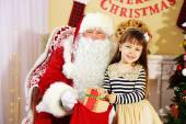 Santa Claus giving  present to  little cute girl near Christmas tree at home — Stock Photo