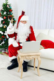 Santa Claus using computer — Stock Photo