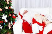 Santa Claus sleeping at home near Christmas tree — Stock Photo