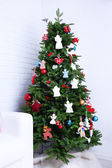 Knitted Christmas angels and other decorations on Christmas tree background, on light background — Stock Photo