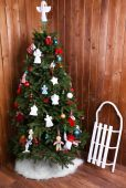 Knitted Christmas angels and other decorations on Christmas tree background, on wooden wall background — Stock Photo