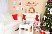 Beautiful Christmas interior with sofa, decorative fireplace and fir tree — Stock Photo