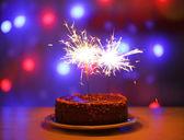 Tasty cake with sparklers on shiny background — Stock Photo