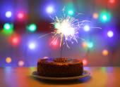 Tasty cake with sparkler on shiny background — Stock Photo