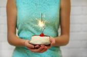 Woman holding tasty cake with sparkler, on grey wall background — Stock Photo