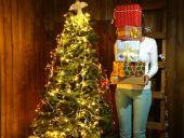 Femme tenant des tas de boîtes présents près de sapin de Noël sur fond de mur en bois — Photo