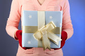 Gift box in female hand on color background — Stock Photo