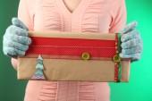 Geschenkkarton in weiblicher Hand auf farbigem Hintergrund — Stockfoto