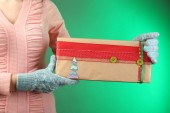 Gift box in female hand on color background — Stockfoto