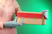 Gift box in female hand on color background — Стоковое фото