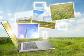 Laptop and images of nature on field and sky background — 图库照片