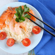 Boiled rice and shrimps, salmon on plate, on wooden background — Stock Photo #61302981