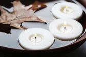Tree white candles floating with leaf on water in bowl — Stock Photo