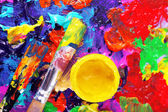 Cans of paint and brush on colorful painted background — Stock Photo