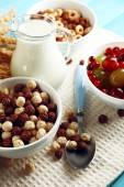 Various sweet cereals in ceramic bowls, fruits and jug with milk on napkin, on color wooden background — Stock Photo