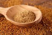 Mustard powder in wooden spoon on mustard seeds, on  wooden background — Stock Photo