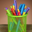 Colorful pens in green metal holder on wooden table and shaded color background — Stock Photo #61311835