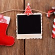 Blank photo frame and Christmas decor on rope, on wooden background — Stock Photo #61312535