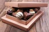 Box filled with chocolates on wooden rustic background — Stock Photo
