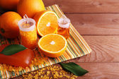 Spa still life with oranges, bottles of bath salt and oil, and bar of soap on striped napkin on wooden background — Stock Photo