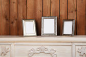 Photo frames on chest of drawers, on wooden wall background — Stockfoto