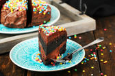 Chocolate cake with colorful sweet powder on table close-up — Stock Photo