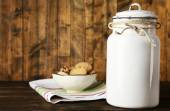 Milk can with bowl of cookies on dishcloth on rustic wooden background — Stock Photo