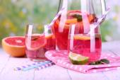Pink lemonade in glasses and pitcher on table on natural background — Stock Photo