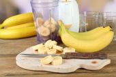 Sliced banana on cutting board, on wooden table, on bright background — Stock Photo