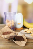 Sliced banana on cutting board and chopped chocolate, on wooden table, on bright background — Stock Photo