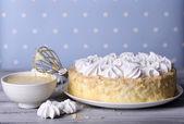 Tasty homemade meringue cake on wooden table, on blue background — Stock Photo