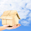 Woman hands holding house wrapped in brown kraft paper on sky background — Stock Photo #61327269