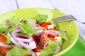 Fresh fish salad with vegetables on plate on wooden table close-up — Stock Photo