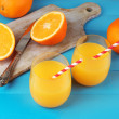 Glass of orange juice with straws and slices on cutting board with knife on color wooden background — Stock Photo #61370385