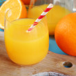 Glass of orange juice with straw and slices on cutting board on color wooden background — Stock Photo #61370393