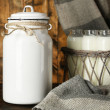 Milk can and glass bottles on rustic wooden background — Stock Photo #61374699