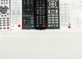 Many remote control devices on table — Stock Photo