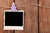 Blank photo frame and Christmas decor on rope, on wooden background — Foto de Stock