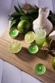 Spa composition with lime and compress balls on bamboo mat and color wooden background — Stock Photo