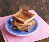 Pane tostato sulla zolla blu con tovagliolo rosa, sul fondo della tavola in legno — Foto Stock
