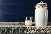 Milk can and glass on color wooden background — Stock Photo
