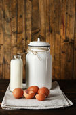 Milk can with eggs, eggshell and glass bottle  on rustic wooden background — Stock Photo