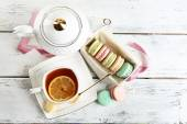 Colorful macaroons with cup of tea on wooden background — Stock Photo
